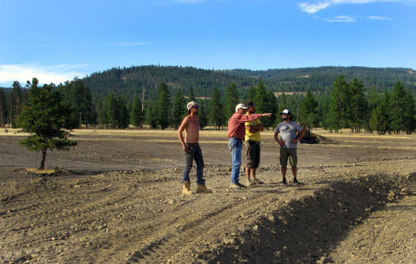 <p>Landowner Craig Woodward (center) gives festival workers directions on earth moving form the top of the earthen amphitheater he shaped from a previously scraped part of land.</p>
