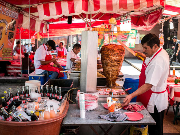 Tacos al pastor, a classic Mexican street food with the meat cooked on a spit, is prepared just outside the Bellas Artes metro station in Mexico City.