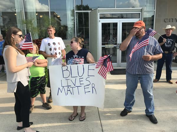 Regina Noland (with sign) organized the small Blue Lives Matter rally outside Bloomington City Hall on Monday evening.