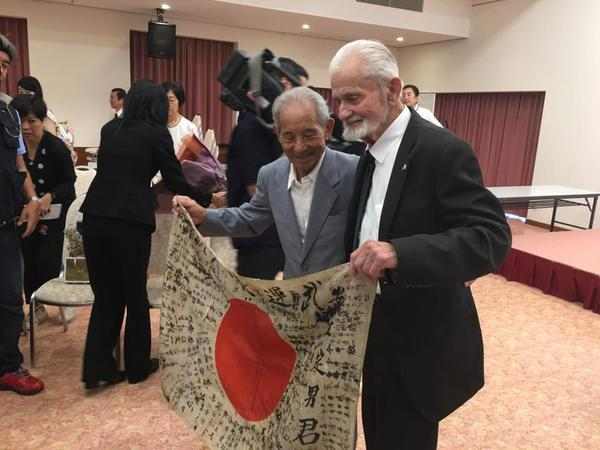 Marvin Strombo, a 93 U.S. veteran of World War II, returned a Japanese ''good luck flag'' to Tatsuya Yasue, left, on Tuesday. Strombo plucked the flag from the body of Yasue's older brother after a battle on Saipan in 1944.