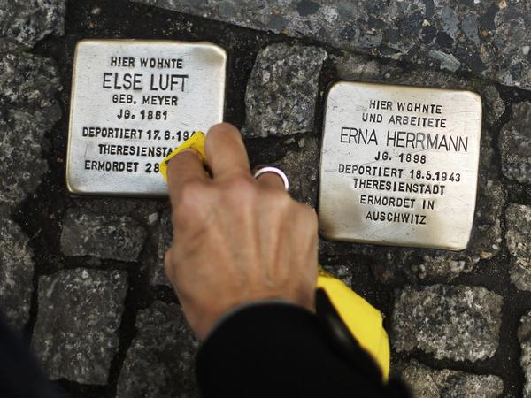 "A woman cleans a <em>Stolperstein</em>, or ""stumbling stone,"" placed in the sidewalk in front of houses where victims of the Holocaust lived before they were deported and killed by the Nazis."