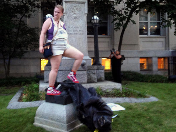 Claire Meddock, 21, stands on a toppled Confederate statue on Monday in Durham, N.C. Activists used a rope to pull down the monument outside a courthouse. The protest was in response to a white nationalist rally held in Charlottesville, Va., over the weekend.