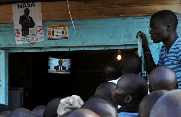 Raila Odinga's supporters in Nairobi gather at an electronics repair shop to watch his Wednesday news conference. Beside the television is a poster for Odinga's political coalition, the National Super Alliance.