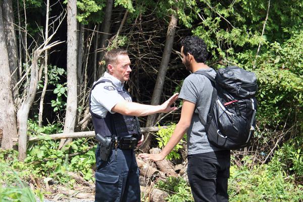A Canadian police officer warns a young man from Yemen that if he illegally crosses into Canada in between checkpoints he will be arrested. If he proves to not be a threat to the public, the officers will help him fill out the asylum request paperwork.