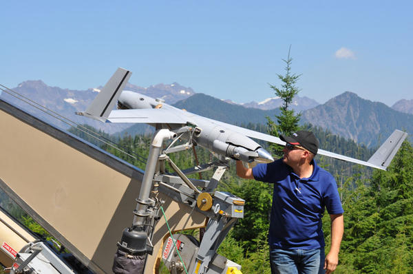 Insitu operator Joseph Cooper prepares the ScanEagle UAS for launch to surveil the Paradise Fire in Olympic National Park in August 2015.