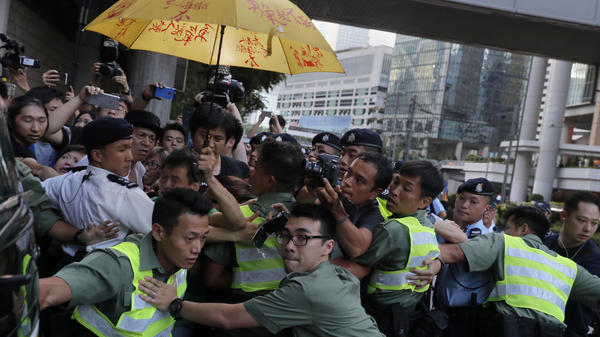 Officers try to clear the way for a prison bus carrying Joshua Wong outside Hong Kong's high court on Thursday.
