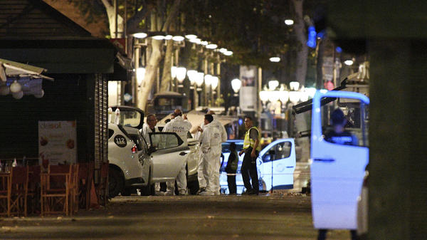 As night falls in Barcelona, Spain, police officers and forensics experts continue to investigate Thursday afternoon's deadly van attack on the popular pedestrian boulevard Las Ramblas.