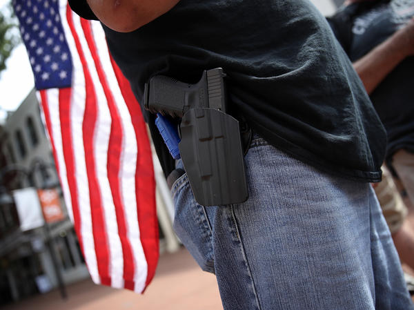 A protester wears a pistol in Charlottesville, Va., on Saturday. The ACLU says it will consider the potential for violence when evaluating whether to represent potential clients.