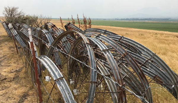 Stacked irrigation wheels line a barb wired fence in Baker County, Oregon.