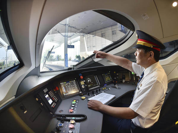 A train driver prepares to operate the Fuxing bullet train as it travels from Tianjin to Beijing.