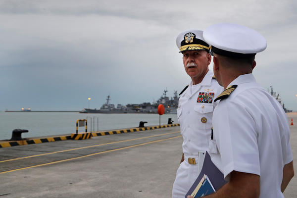 With the USS John McCain docked in the background at Singapore's Changi naval base, Pacific Fleet commander Adm. Scott Swift (left) heads to a press conference on Tuesday.