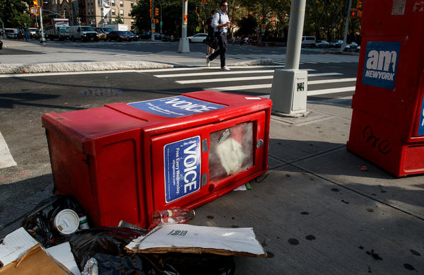 A<em> Village Voice</em> newspaper stand lays on the ground next to garbage in New York City's East Village on Tuesday. <em>The</em> <em>Village Voice</em>, one of the oldest and best-known alternative weeklies in the U.S., announced that it will no longer publish a print edition.