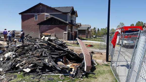 Workers dismantle the charred remains of a home where an unrefined petroleum industry gas-line leak explosion killed two people inside their home in Firestone, Colo.