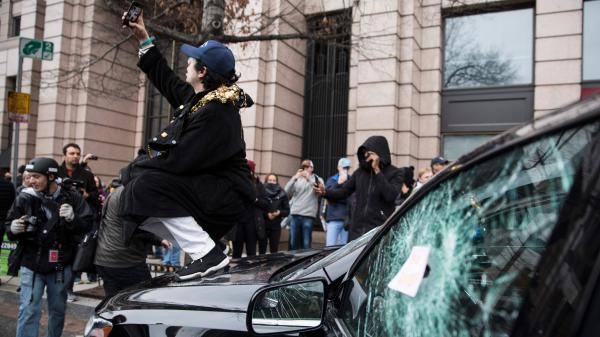 A man takes a selfie on the hood of a destroyed limousine during an Inauguration Day protest against President Trump on Jan. 20 in Washington, D.C. The Department of Justice has been cleared to search through website records related to organizing protests that day.