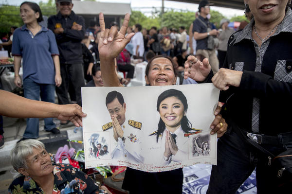Supporters hold a poster of former Thai Prime Ministers Yingluck Shinawatra (right) and Thaksin Shinawatra as they demonstrate outside the Supreme Court in Bangkok on Friday. A Thai court issued an arrest warrant for Yingluck after she didn't attend a hearing in her negligence trial.