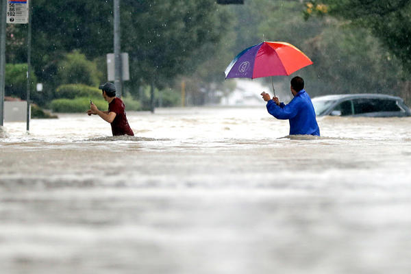 Moses Juarez, left, and Anselmo Padilla wade through floodwaters from Tropical Storm Harvey on Sunday in Houston.