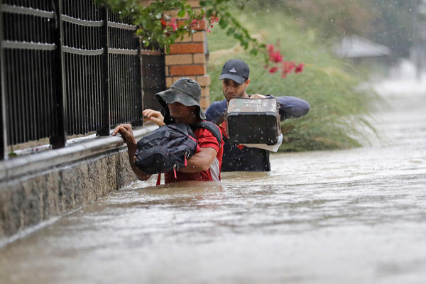 Residents wade through floodwaters from Tropical Storm Harvey Sunday in Houston, Texas.