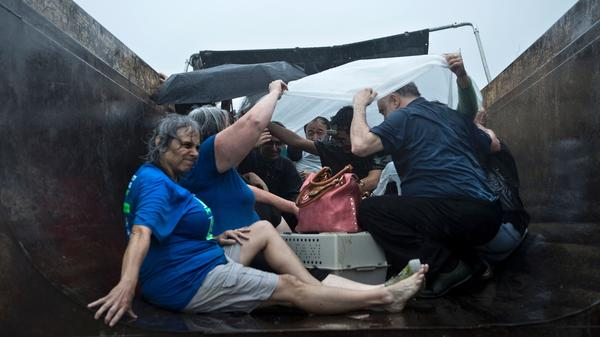 People wait to be taken out in a city dump truck on an overpass in Houston on Sunday. The most powerful storm to hit the U.S. in years, Hurricane Harvey left a trail of devastation across Texas over the weekend, destroying homes, severing power supplies and forcing tens of thousands of residents to flee.