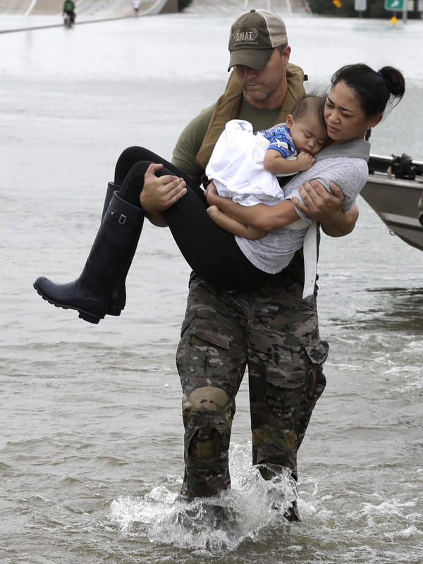 Houston police SWAT Officer Daryl Hudeck carries Catherine Pham and her 13-month-old son to safety. He rescued them from their home, which had been surrounded by floodwaters Sunday.