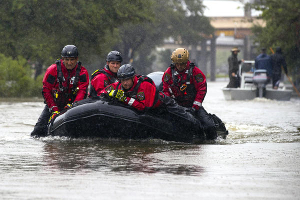 Houston Fire Department Dive Team members motor through high water looking for victims of the flooding from Hurricane Harvey.