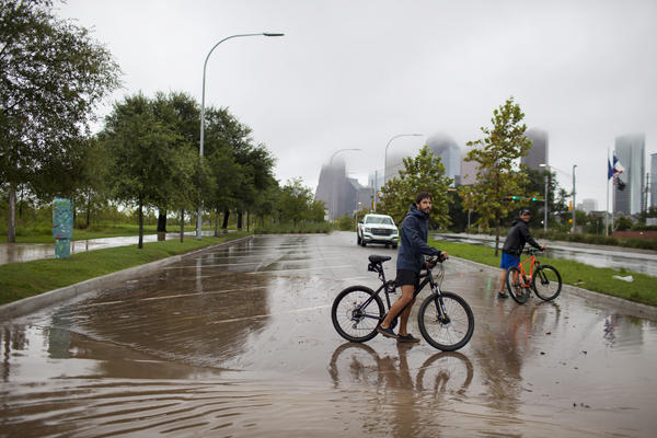 "Houston residents Julian Fernandez (left) and Simon Loscertales survey the flooding next to Buffalo Bayou Park in Houston. ""I am now a refugee,"" says Fernandez, whose neighborhood has flooded."