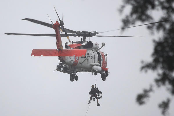 A Coast Guard helicopter hoists a wheel chair on board after lifting a person to safety from the area that was flooded in Houston.