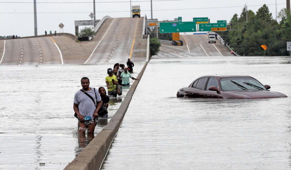 <p>Evacuees wade down a flooded section of Interstate 610 as floodwaters from Tropical Storm Harvey rise Sunday, Aug. 27, 2017, in Houston.</p>