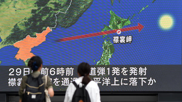 Passers-by look at the North Korean missile's path over Japan, displayed on a huge screen in Tokyo on Wednesday. Japanese Prime Minister Shinzo Abe said he and President Trump have agreed to increase pressure on Kim Jong Un's regime after it launched a ballistic missile over the Japanese island of Hokkaido.