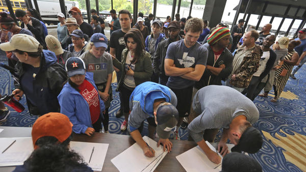 Volunteers sign up to help those seeking shelter from the flooding caused by Tropical Storm Harvey at Lakewood Church on Tuesday.