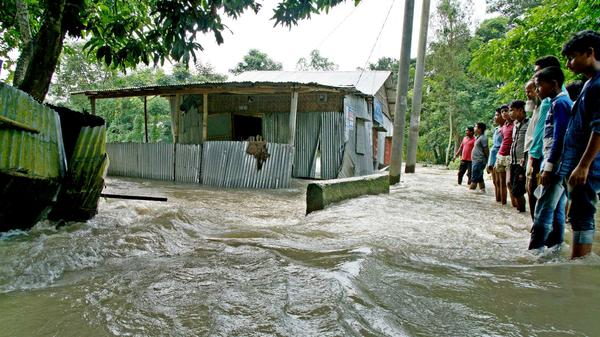 Bystanders look on as floodwaters rage near a house in Kurigram, northern Bangladesh, in mid-August. Tens of millions of people are affected by what aid agencies are calling the region's worst monsoon disaster in recent years.