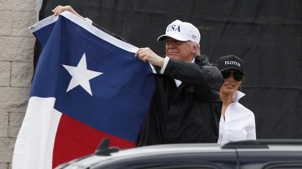 Trump holds up a Texas flag after speaking with supporters outside Firehouse 5 in Corpus Christi, Texas, where he also received a briefing from state and local officials.