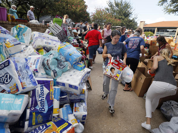 Volunteers organize stacks of donations that were dropped off Tuesday at the North Dallas location for Hurricane Harvey victims.