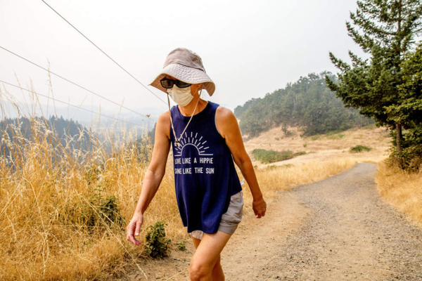 <p>Lisa Bedortha hikes up Mount Pisgah outside Eugene wearing a dust mask.</p>