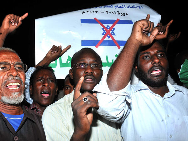Sudanese demonstrators hold banners and chant anti-Israeli slogans during a protest in Khartoum on Wednesday, following a missile strike that hit a factory. Sudan blames Israel for the attack. Israel has not commented on the charge.