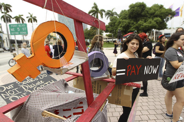 Women stage a protest demanding equal pay for women at a 2012 rally in Miami.