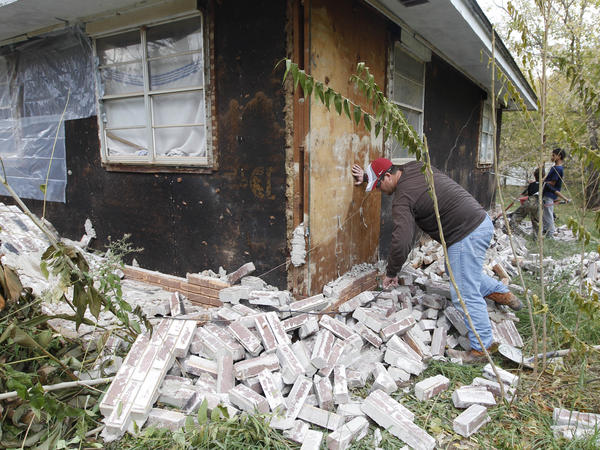 Chad Devereaux examines bricks in November 2011 that fell from three sides of his in-laws home in Sparks, Okla., following two earthquakes that hit the area in less than 24 hours. The state earlier this week acknowledged that many recent earthquakes in the state were the result of underground disposal of wastewater from oil and gas drilling.