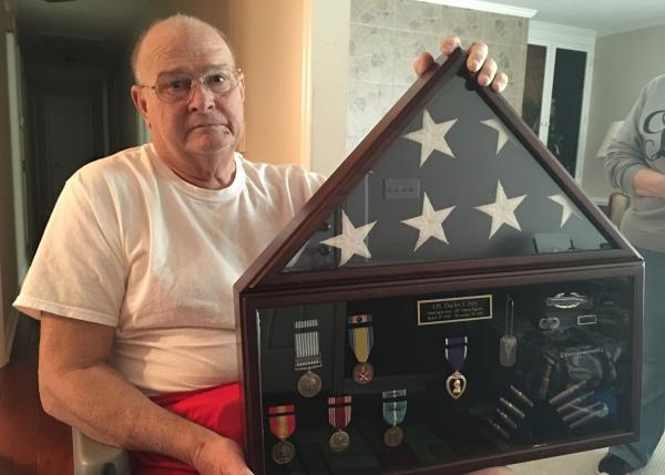 Harold Ivey holds the military medals of his brother Charles, who died in the Korean War.