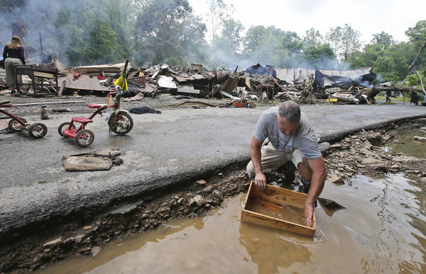 Mark Lester cleans out a box with creek water as he cleans up from severe flooding in White Sulphur Springs, W. Va., on Friday.