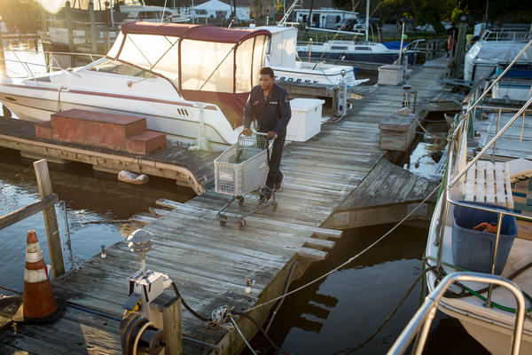 """James """"AJ"""" Hall walks down the dock at Seafarers to his boat, <em>The Raven</em>, on a Sunday evening in autumn of 2015. He died a little over a year later."""