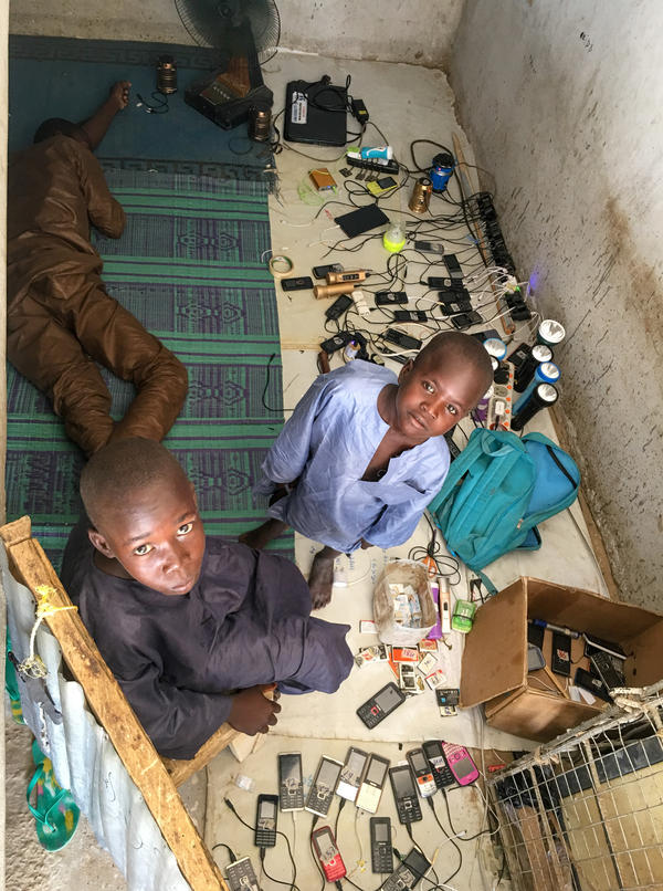 Churi has set up shop in the stairwell of an unfinished three-story brick building that has been taken over by displaced people in Nigeria.