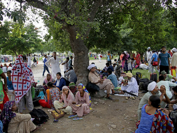 """Supporters of the Dera Sacha Sauda sect wait near an Indian court in Panchkula last Thursday, a day before their spiritual leader Gurmeet Ram Rahim Singh was convicted of rape. Many of Singh's supporters are low-caste or Dalits, previously known as """"untouchables,"""" who turned to his ashram for basics such as food and medicine."""