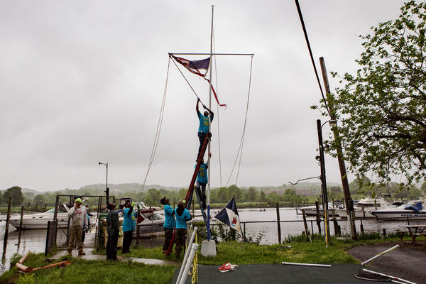 Seafarers' members work together to take down a wind-tattered American flag on Earth Day, 2017.