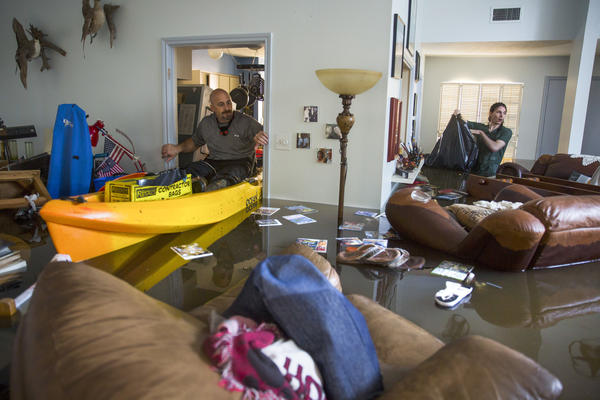 Larry Koser Jr. (left) and his son, Matthew, look for important papers and heirlooms inside his house after it was flooded by heavy rains from Hurricane Harvey.