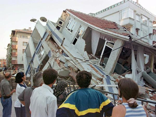 Earthquake survivors look at a collapsed building in Istanbul in August 1999. The magnitude 7.4 quake killed 17,000 people across northwestern Turkey.