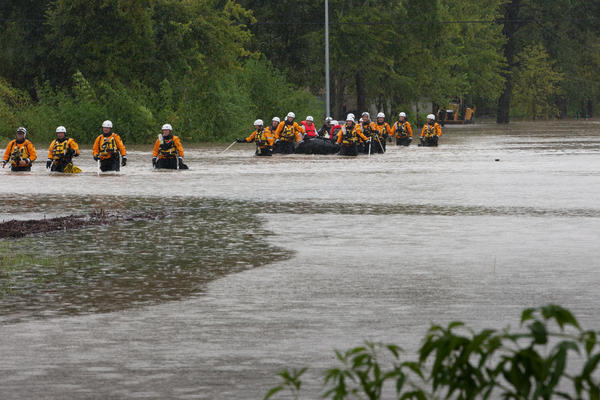 A search and rescue team pulls people out of an area flooded by the overflow of Addicks Reservoir in Houston on Tuesday.