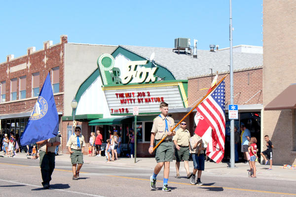 Local Boy Scouts carry flags down Illinois Street in a parade marking the 150th anniversary of the founding of the city of Sidney, Nebraska.