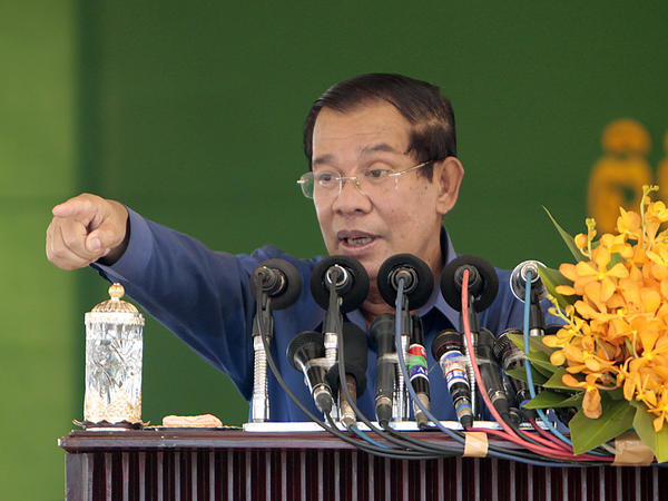 "Cambodia's Prime Minister Hun Sen speaks to garment workers during a visit to a factory outside Phnom Penh on Aug. 30. His government has slapped the English-language <em>Cambodia Daily </em>with a $6.3 million tax bill and ordered it to pay by Sept. 4. If it doesn't, Hun Sen said, it should ""pack up and go."""
