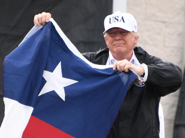 Trump holds the state flag of Texas outside the Annaville Fire House after attending a briefing on Hurricane Harvey in Corpus Christi, Texas, on Tuesday.
