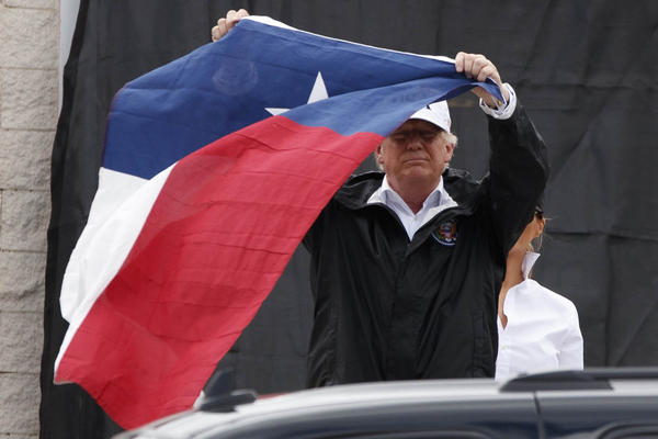 President Donald Trump holds up a Texas flag after speaking with supporters outside Firehouse 5  in Corpus Christi, Texas, Tuesday, Aug. 29, 2017. (Evan Vucci/AP)