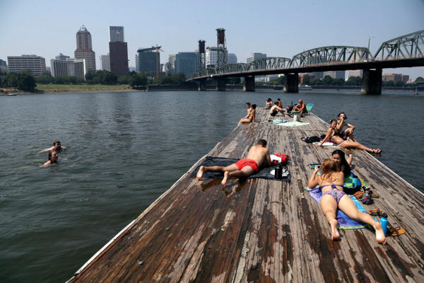 <p>People sunbathe and cool off in the Willamette River with the downtown skyline visible in the background in Portland, Ore., Wednesday, Aug. 2, 2017.</p> <p> </p>